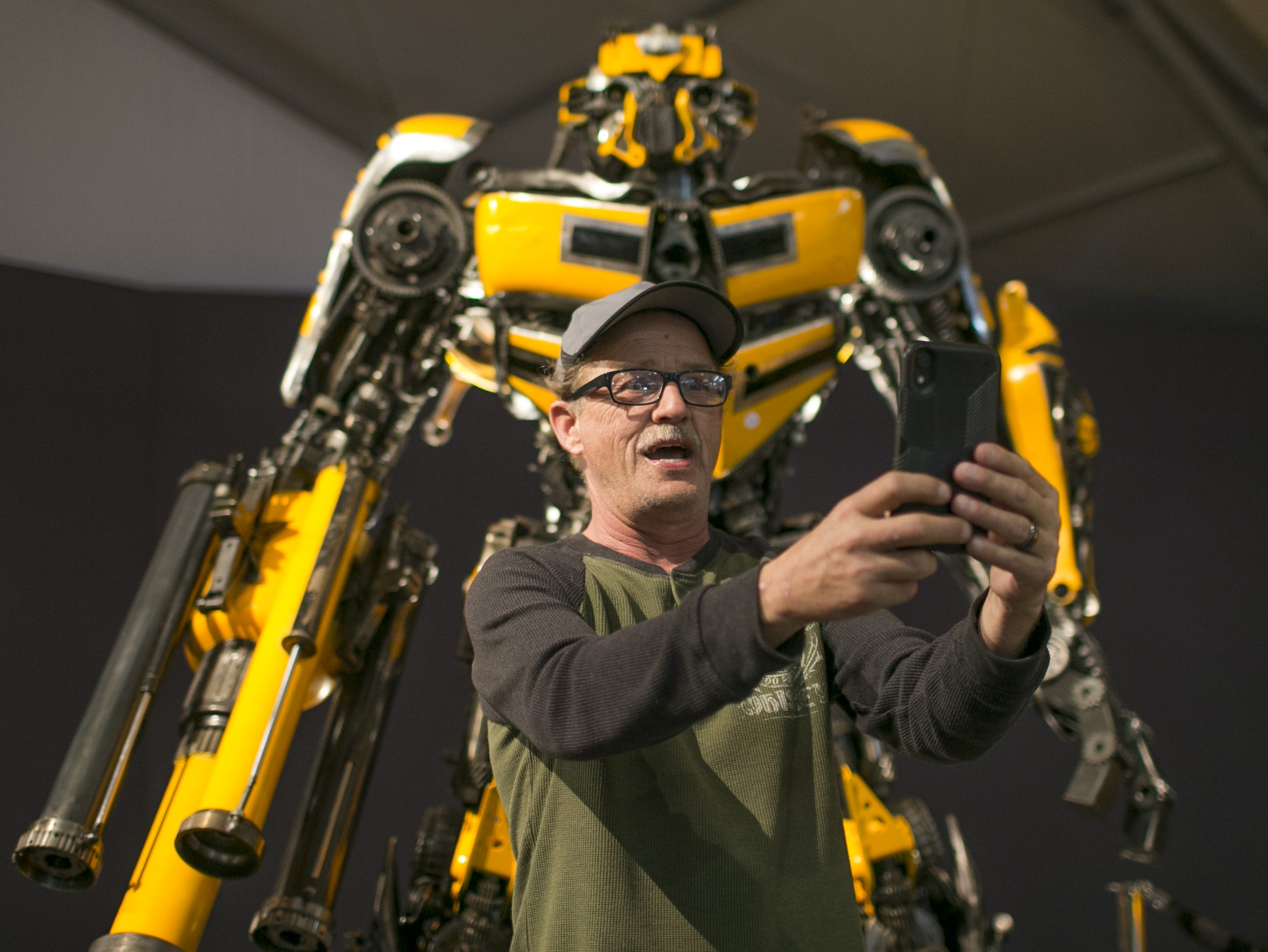 Dwayne Magill takes a selfie with a statue of Bumblebee from the Transformers movie franchise at the Barrett-Jackson Car Auction at WestWorld in Scottsdale, Arizona, on Jan. 16, 2019.