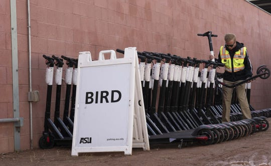 An ASU employee brings impounded electric scooters to the campus impound lot.