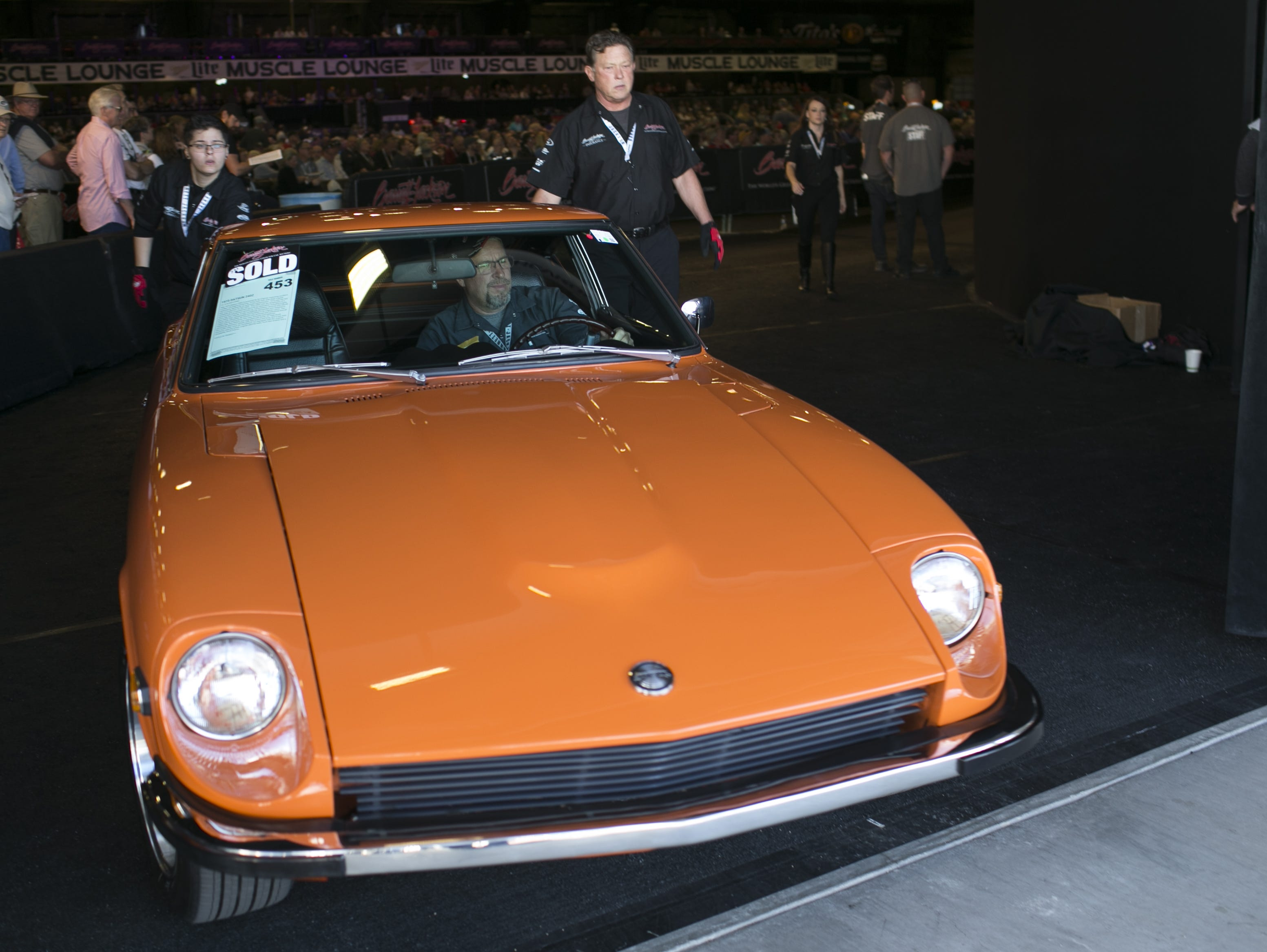 A 1973 Datsun 240Z is driven out of the auction block after being sold at the Barrett-Jackson Car Auction at WestWorld in Scottsdale, Arizona, on Jan. 16, 2019.