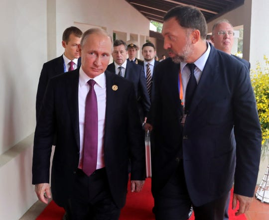 Russia's President Vladimir Putin, left, and Russian metals magnate Oleg Deripaska, right, attend the APEC Business Advisory Council dialogue in Danang, Vietnam, in November 2017.  A joint resolution of disapproval passed by the U.S. House of Representatives on Thursday seeks to overturn the U.S. Treasury Department's decision to ease sanctions on three companies Deripaska controls.