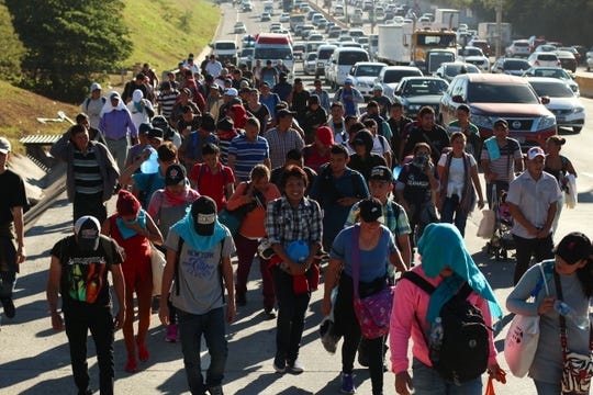Migrants traveling in a group begin their journey toward the U.S. border as they walk along a highway in San Salvador, El Salvador, early Wednesday, Jan. 16, 2019. Migrants fleeing Central America's Northern Triangle region comprising Honduras, El Salvador and Guatemala routinely cite poverty and rampant gang violence as their motivation for leaving.