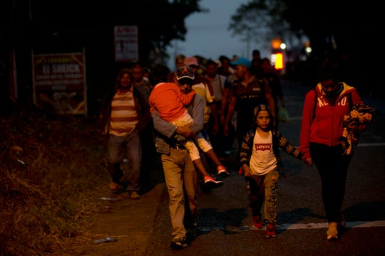 Honduran migrants walk at dawn along the roadside through Esquipulas, Guatemala, as they make their way toward the U.S. border, Wednesday, Jan. 16, 2019. The latest caravan of Honduran migrants hoping to reach the U.S. has crossed into Guatemala.