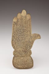 A hand of Fatima (a symbol of feminine power) inscribed with Thuluth script from Algeria or Morocco, created by an unknown artist no later than 1928.