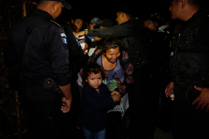 A Honduran migrant family walks between police officers as they enter Guatemala, at the border crossing in Agua Caliente, Tuesday, Jan. 15, 2019. The latest caravan of Honduran migrants hoping to reach the U.S. has crossed peacefully into Guatemala, under the watchful eyes of about 200 Guatemalan police and soldiers.