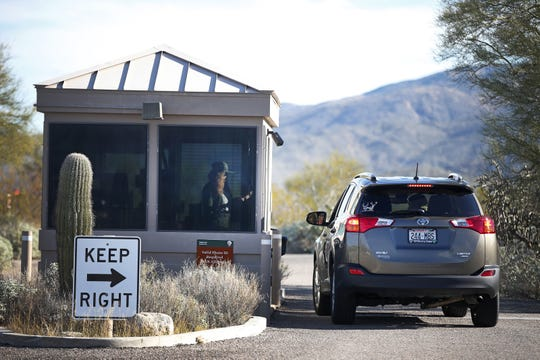 Anna Barney, visitor use assistant for Saguaro National Park in Tucson, answer park use questions on January 16. The park has been able to remain open, operating with a skeleton crew.