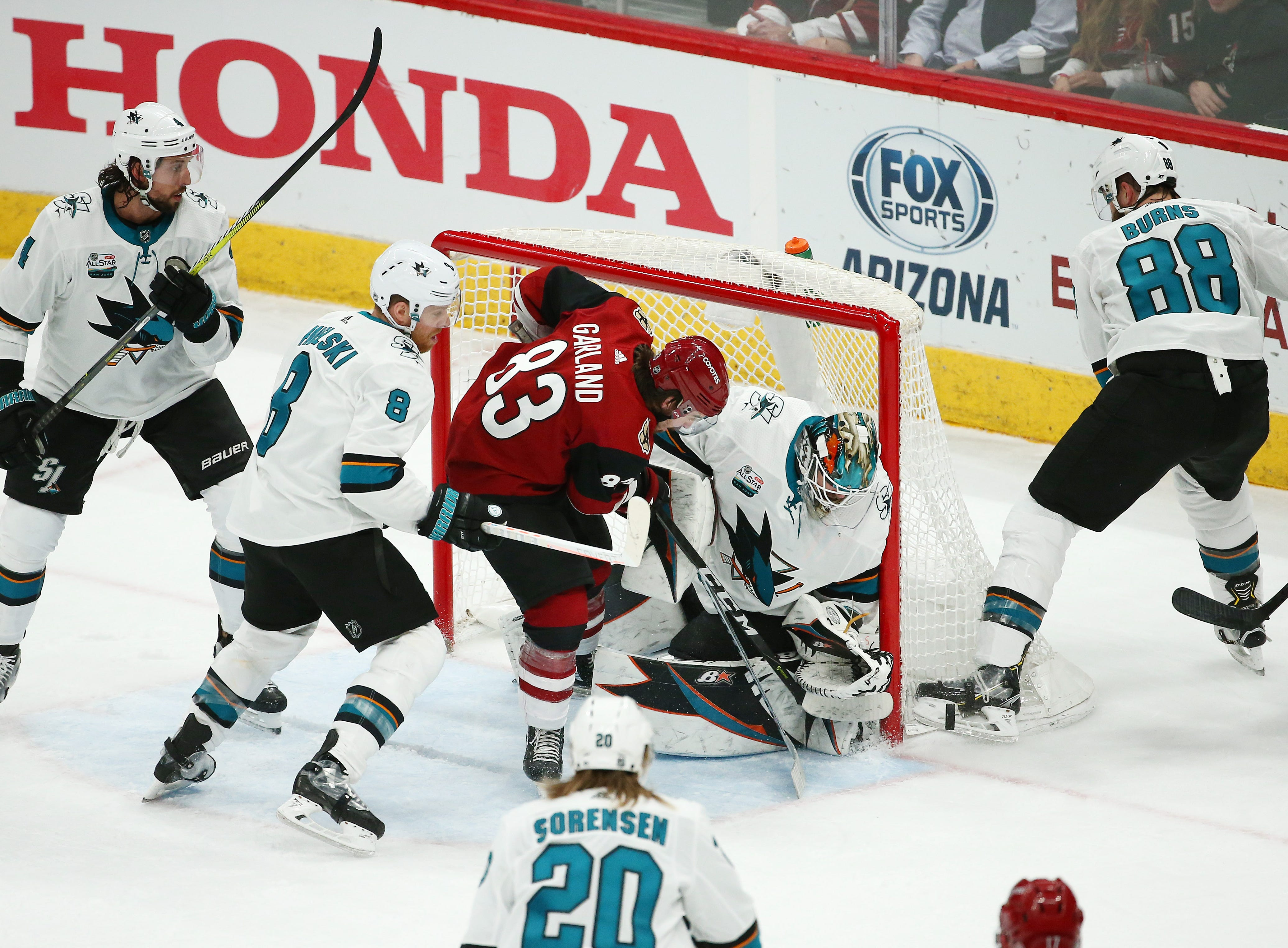 Arizona Coyotes' Conor Garland (83) battles for the puck with San Jose Sharks goalie Aaron Dell in the 1st period on Jan. 16 at Gila River Arena.