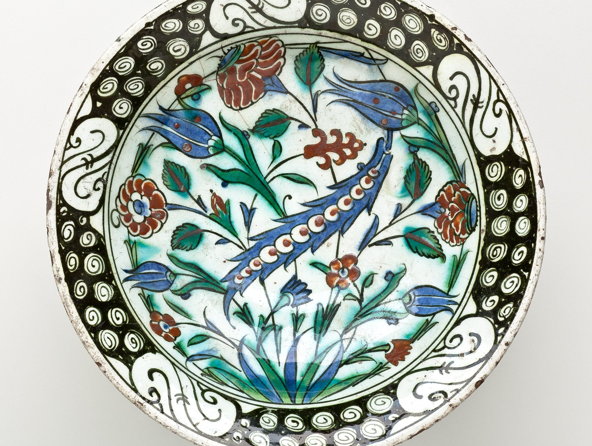 """Red Carnations, Blue Tulips and Blue Saz Leaf on a Dish with Flower Petal Rim,"" Iznik, Turkey, 18th century."