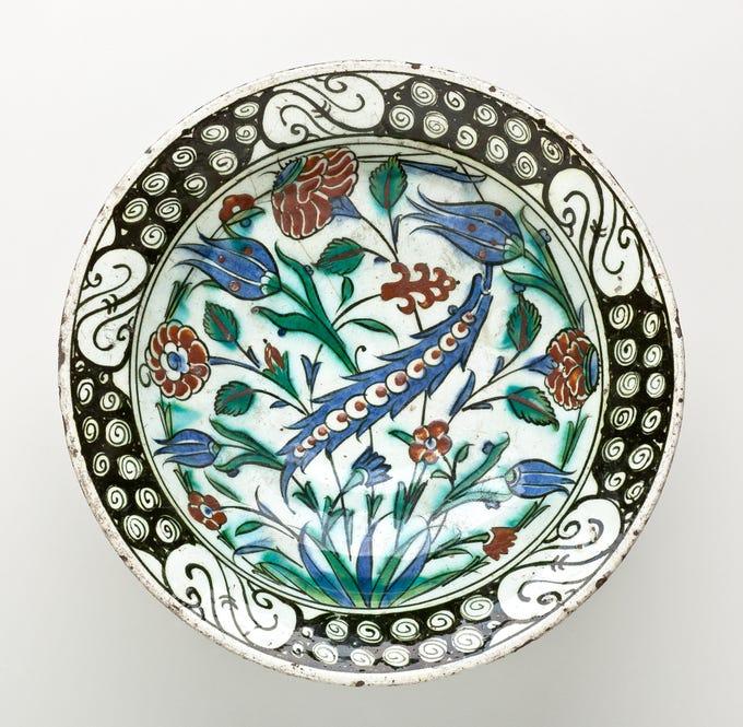 """Red Carnations, Blue Tulips and Blue Saz Leaf on a Dish with Flower Petal Rim,"" Iznik, Turkey, 18th century."