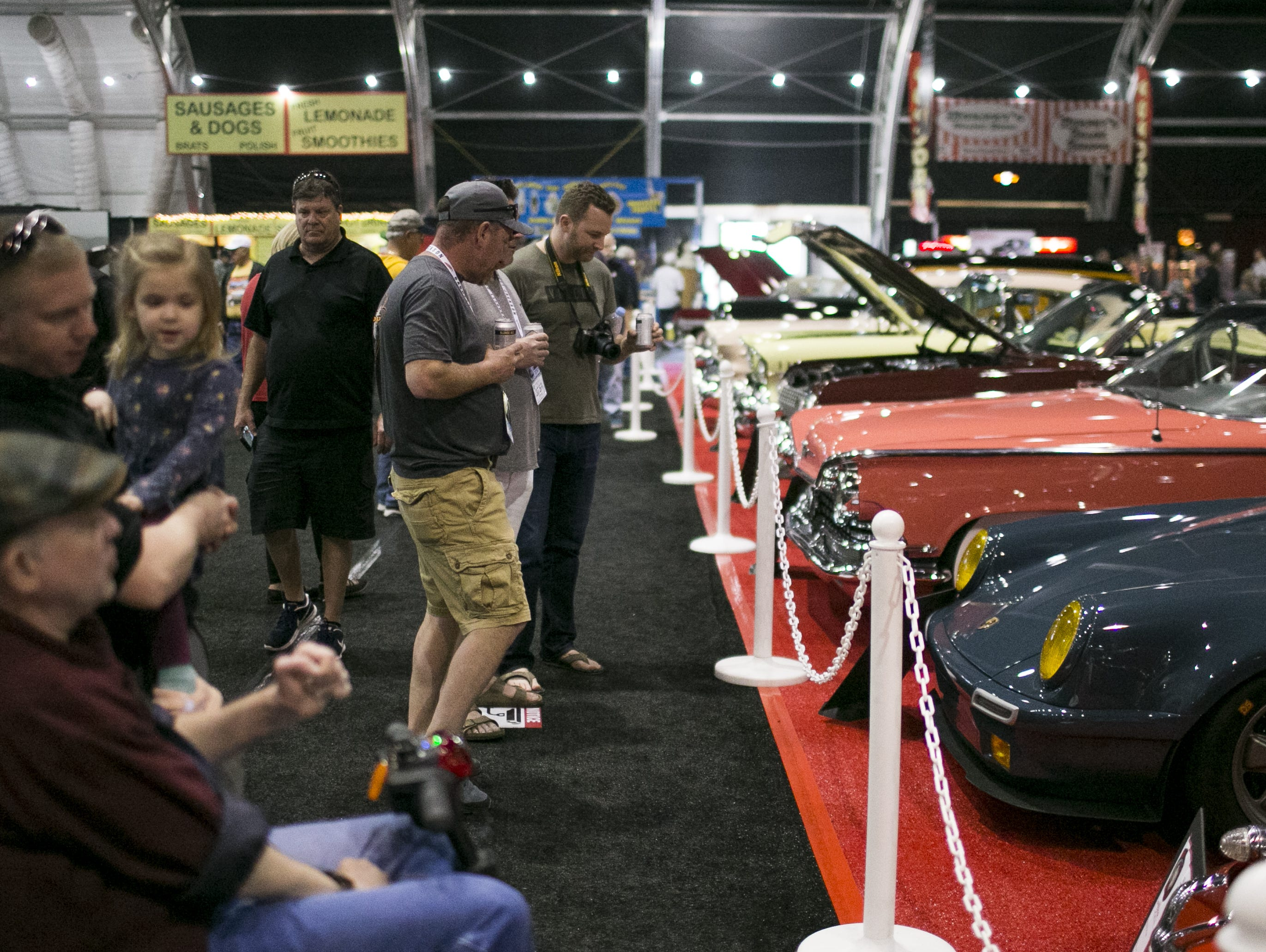 Spectators take photos of and admire classic cars at the Barrett-Jackson Car Auction at WestWorld in Scottsdale, Arizona, on Jan. 16, 2019.