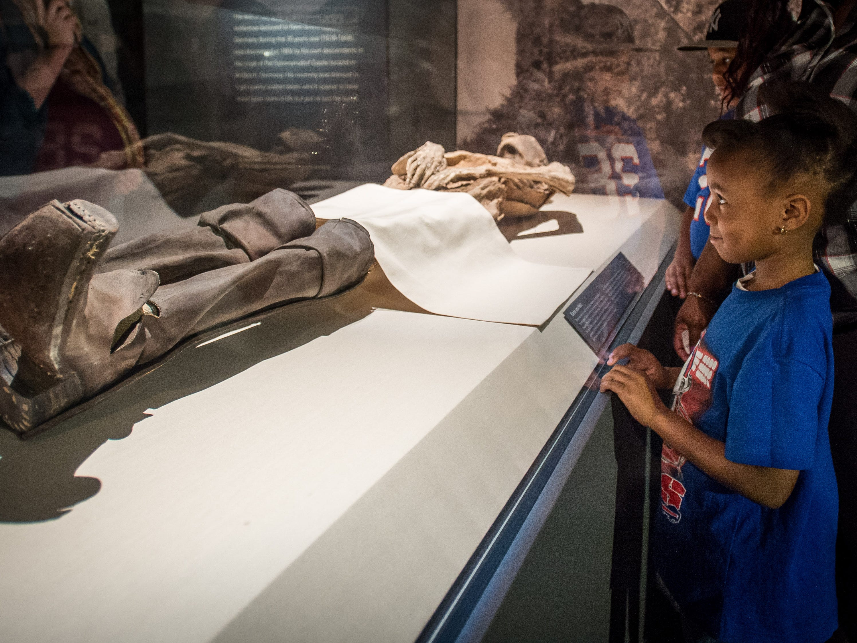 A young girl examines Baron Von Holz, part of the Mummies of the World: The Exhibition display at the Arizona Science Center.