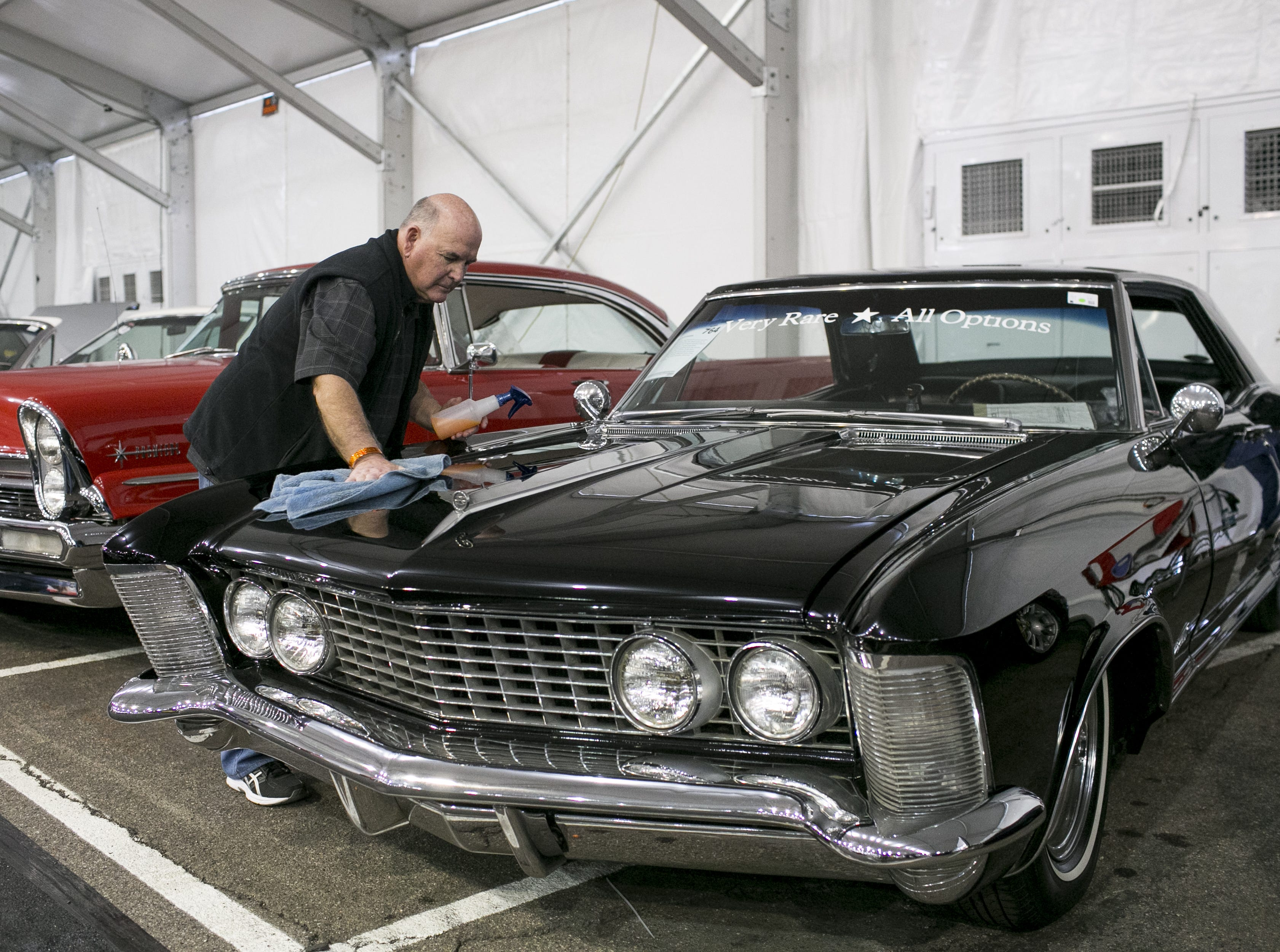 Greg Selvidge (left) cleans his 1964 Buick Riviera at the Barrett-Jackson Car Auction at WestWorld in Scottsdale, Arizona, on Jan. 16, 2019.
