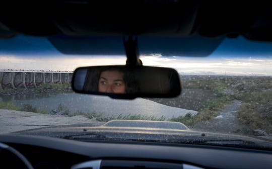 Gaby Caloca, of the Mexican conservation group Pronatura Noroeste, is reflected in her vehicle's rearview mirror, December 7, 2018, at Morelos Dam in Mexico. The dam diverts the last of the Colorado River to Mexican farms and cities.