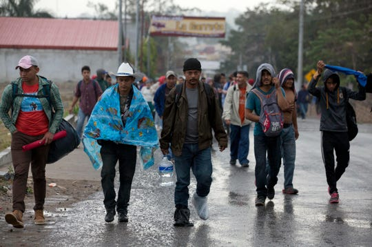 Honduran migrants walk along the roadside through Esquipulas, Guatemala, as they make their way toward the U.S. border, early Wednesday, Jan. 16, 2019. The latest caravan of Honduran migrants hoping to reach the U.S. has crossed into Guatemala. (AP Photo/Moises Castillo)