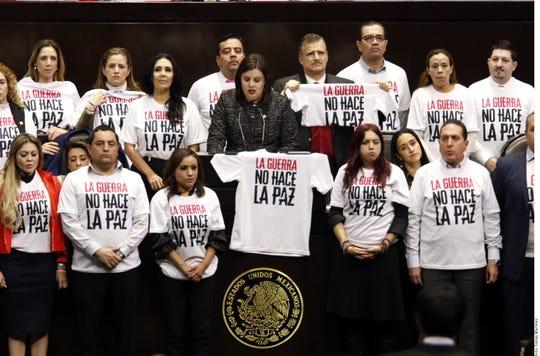 """Durante el debate la fracción parlamentaria de Movimiento Ciudadano (MC) protestó en tribuna con playeras blancas que decían """"La Guerra no hace la Paz""""."""