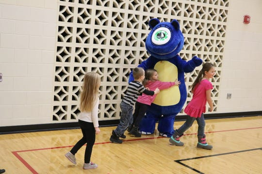 Ero the Hero, Bataan Primary School's new mascot, greets students with hugs and high fives on Wednesday.