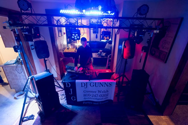 """Flashing lights illuminate the living room of the Port Huron home where Gunner Welch, 14, also known as """"DJ Gunns,"""" plays through a playlist of electronic dance music Wednesday, Jan. 16, 2019. Gunner has been DJing for about a year, and usually performs at weddings, company picnics and private events."""