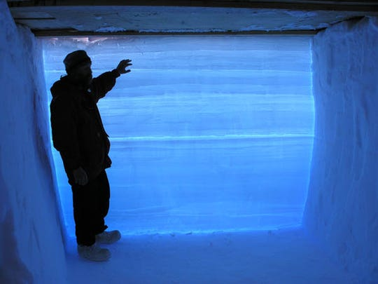 Kendrick Taylor in a snow pit in Antarctica, in front of layers of snow that record past changes in climate.