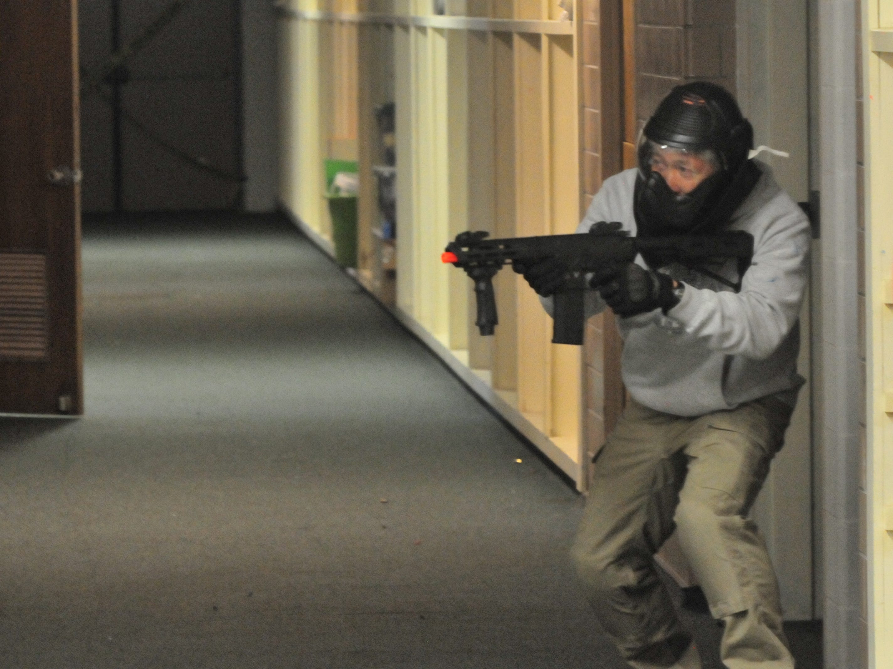 "A ""suspect"" waits to ambush officers during an active-shooter training scenario Wednesday."