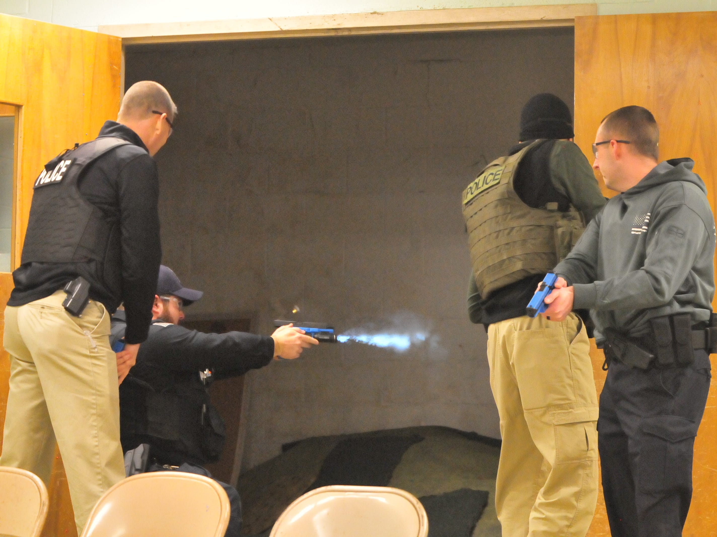 "Participating officers confront a ""suspect"" and fire a simulation weapon at him during an active-shooter scenario Wednesday."
