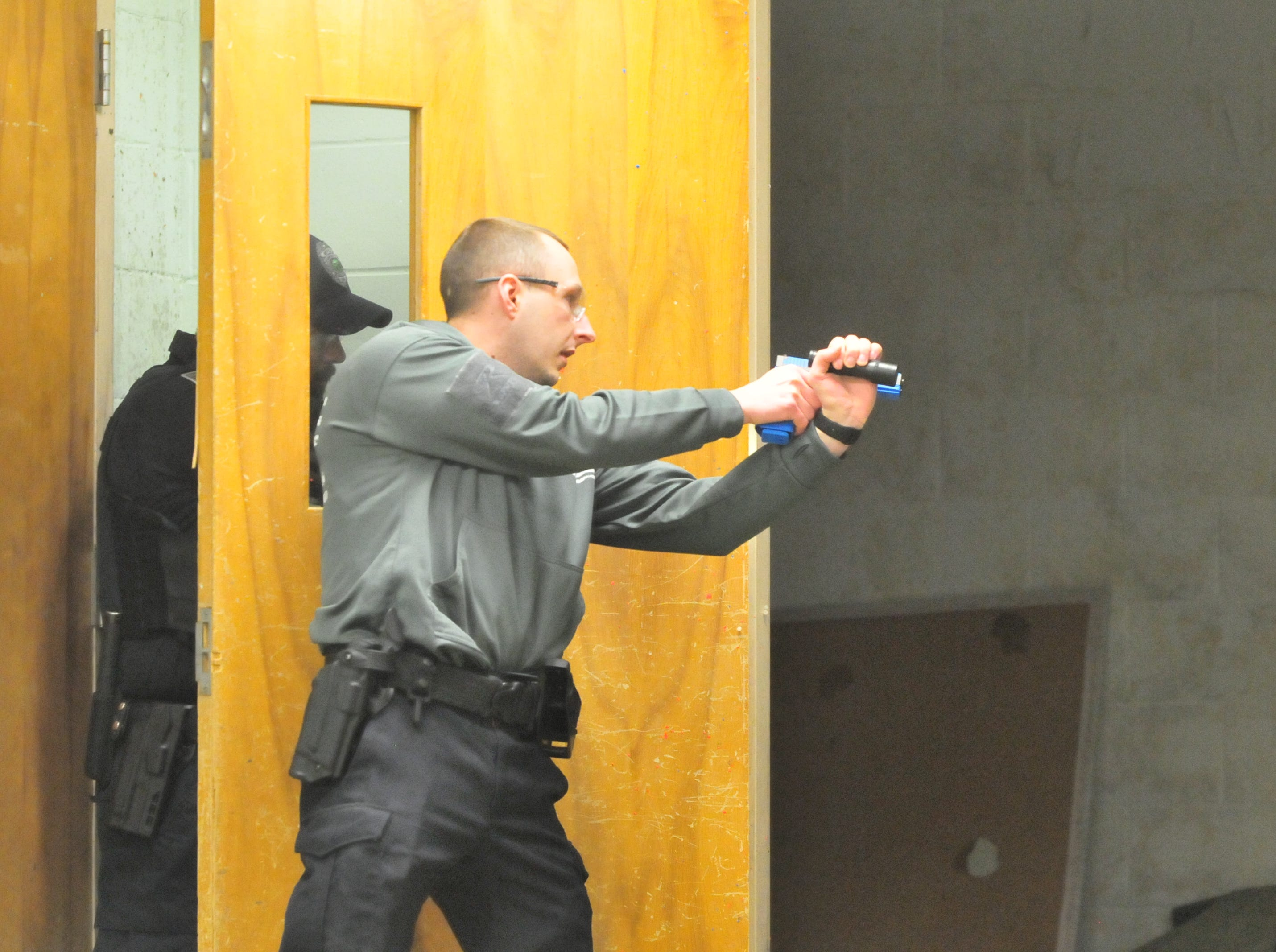 "Officers look through a doorway at a ""suspect"" during an active-shooter scenario Wednesday."