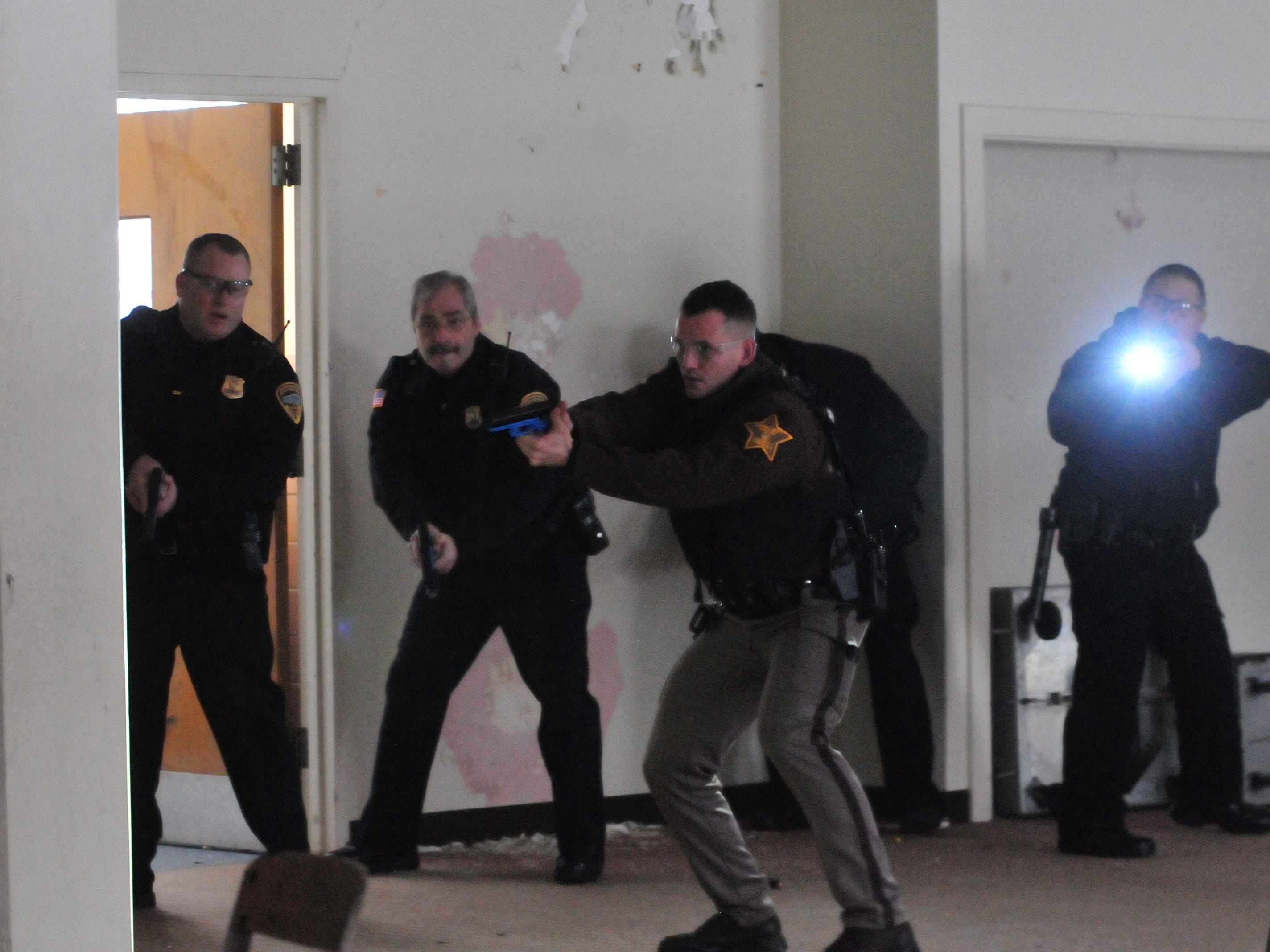 "Officers locate a ""suspect"" behind a table during an active-shooter training scenario Wednesday."