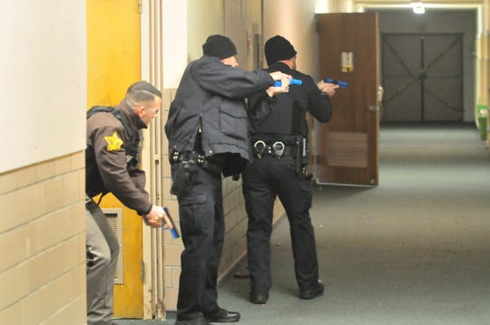 "Officers approach a stairway as they search for ""suspects"" during an active-shooter scenario Wednesday."