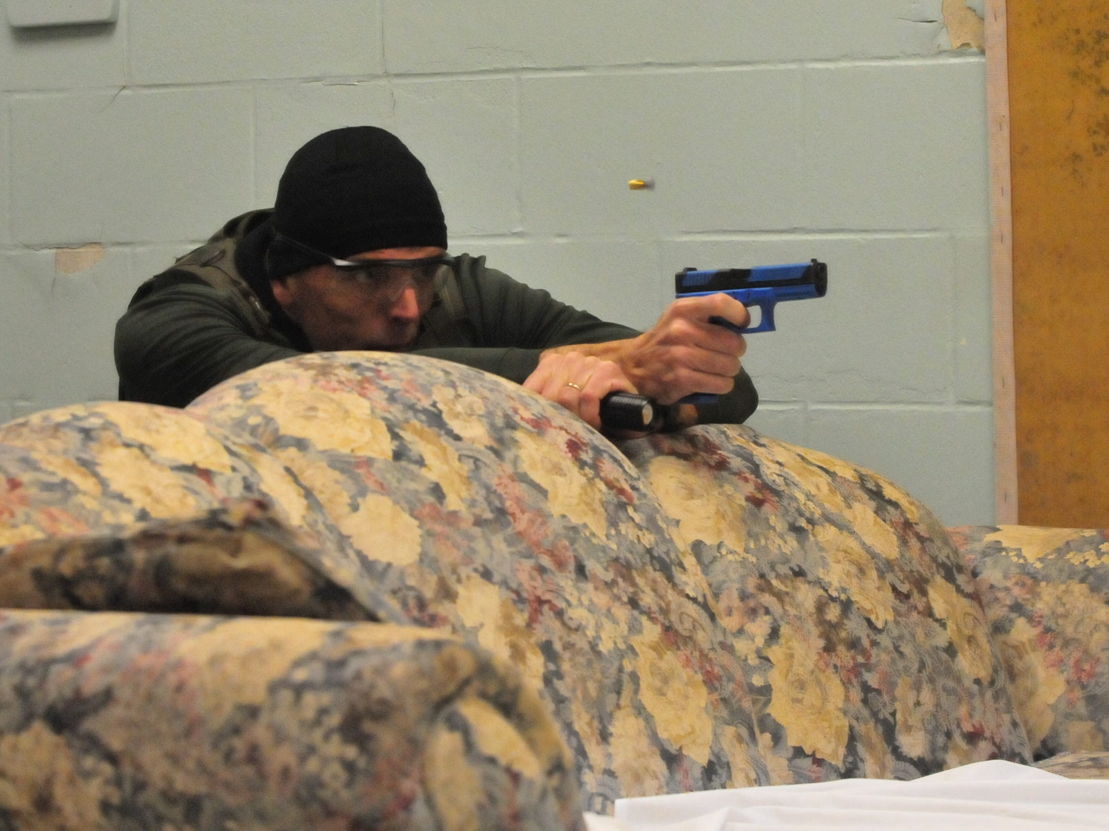 "Richmond Police Department Detective Ron Pennington fires a simulation weapon at a ""suspect"" during active-shooter training Wednesday."