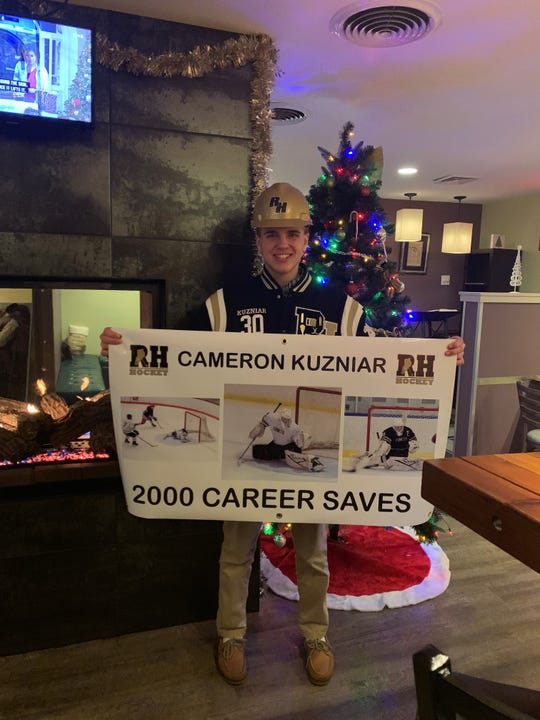 Rush-Henrietta hockey goalie Cameron Kuzniar is shown with the poster his parents held up at the game where he recorded his 2,000th career save.
