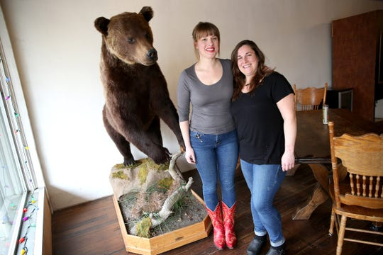 The Valkyrie Wine Tavern's owners Savannah Pearce and Lindsay Darling pose next to a taxidermy bear in their restaurant in Independence on Thursday, Jan. 16 2019. Darling is also the chef at the restaurant.
