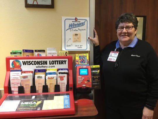 Kwik Trip Store Leader Jan Peters stands near a sign telling customers that Sheboygan location just sold a winning Megabucks lottery ticket worth $5.9 million.