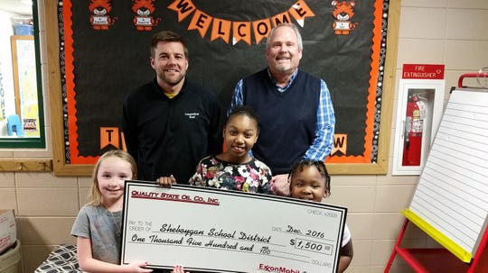 Scott Stangel of Quality State Oil Company poses with Longfellow principal Paul DePagter and students.