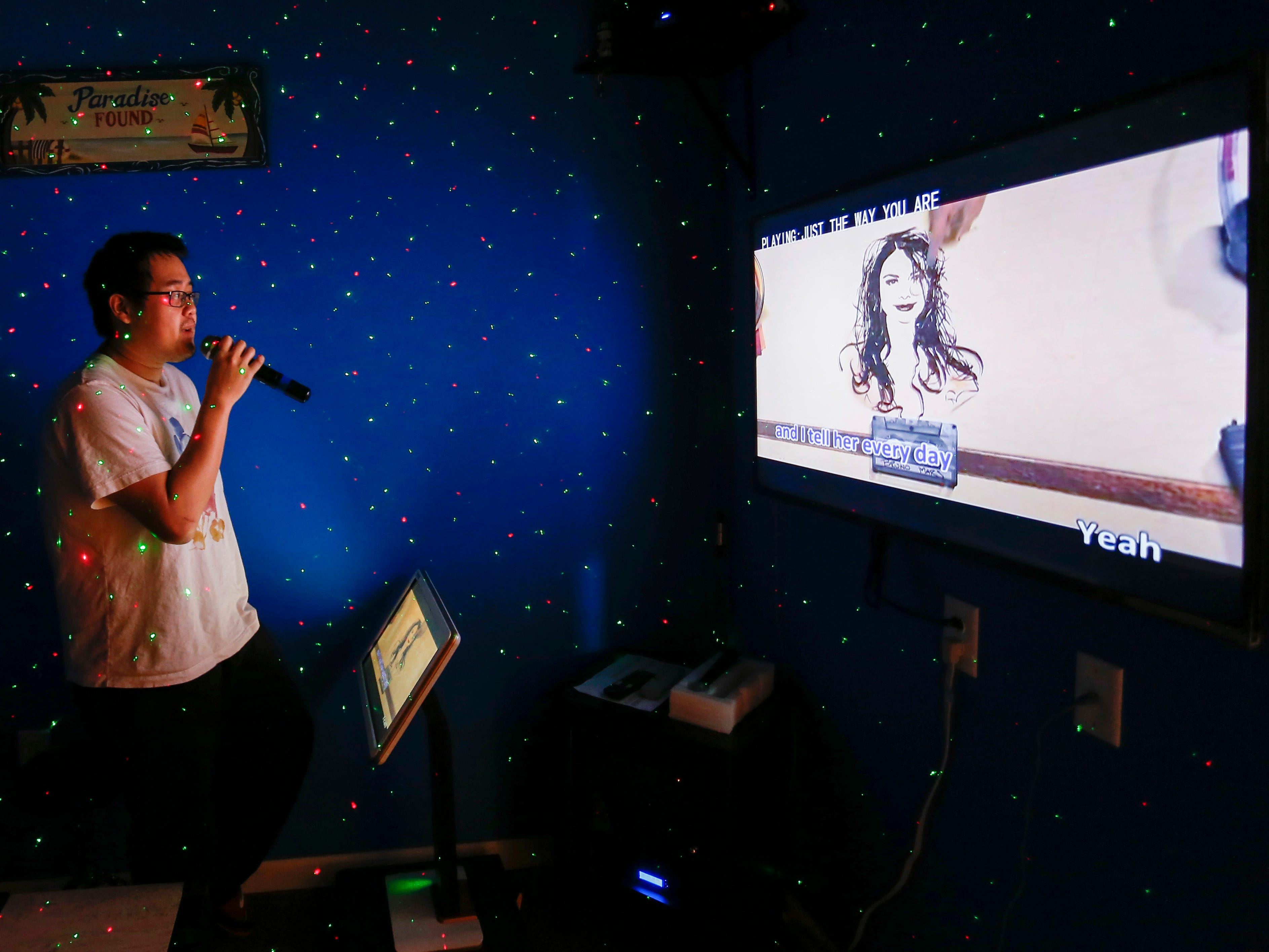Randall Hang, owner of The Hangout, demonstrates how the karaoke machines work by singing a Bruno Mars song at the new karaoke business on Glenstone Ave. on Wednesday, Jan. 16, 2019.