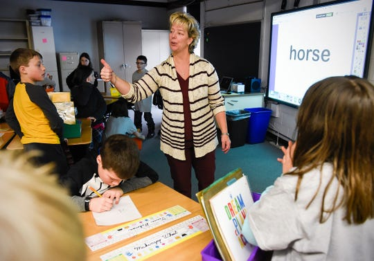 Teacher Val Martin gives a thumbs-up to her third-grade class Tuesday, Jan. 15, in their new classroom after a fire Sunday at Pleasantview Elementary School in Sauk Rapids.