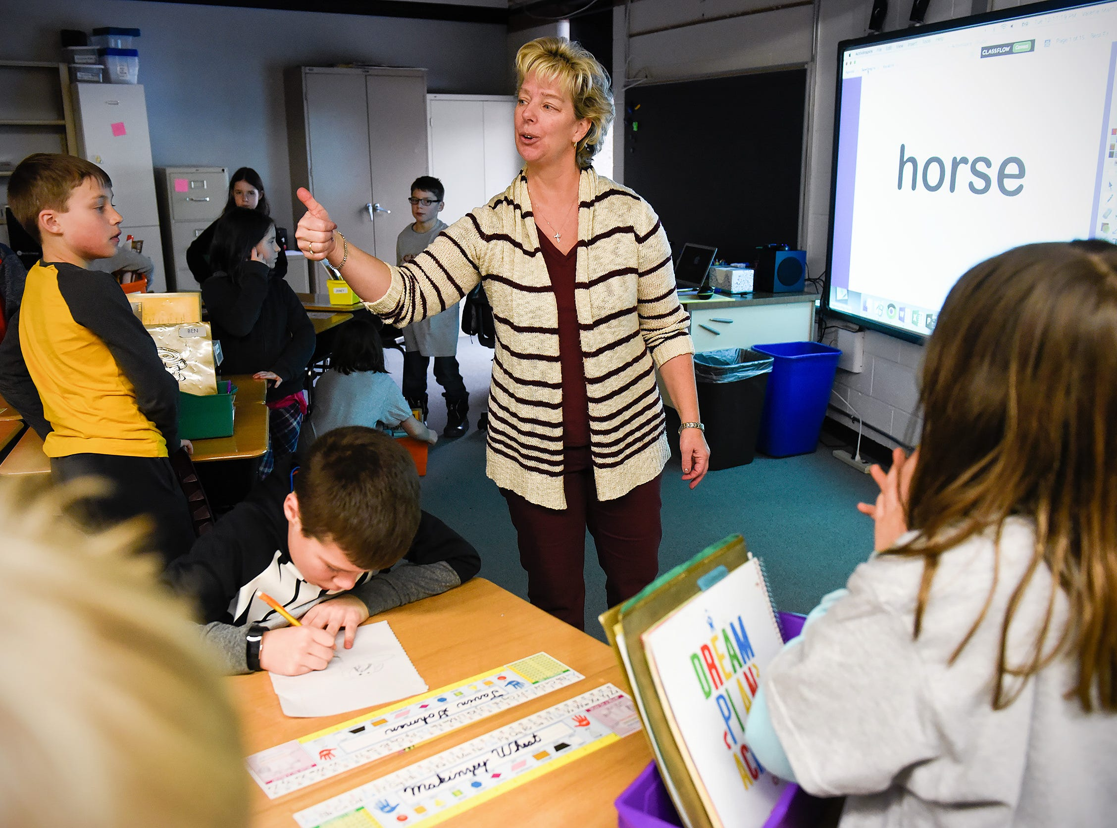 Teacher Val Martin gives a thumbs up to her third grade class Tuesday, Jan. 15, in their new classroom after a fire at Pleasantview Elementary School in Sauk Rapids.