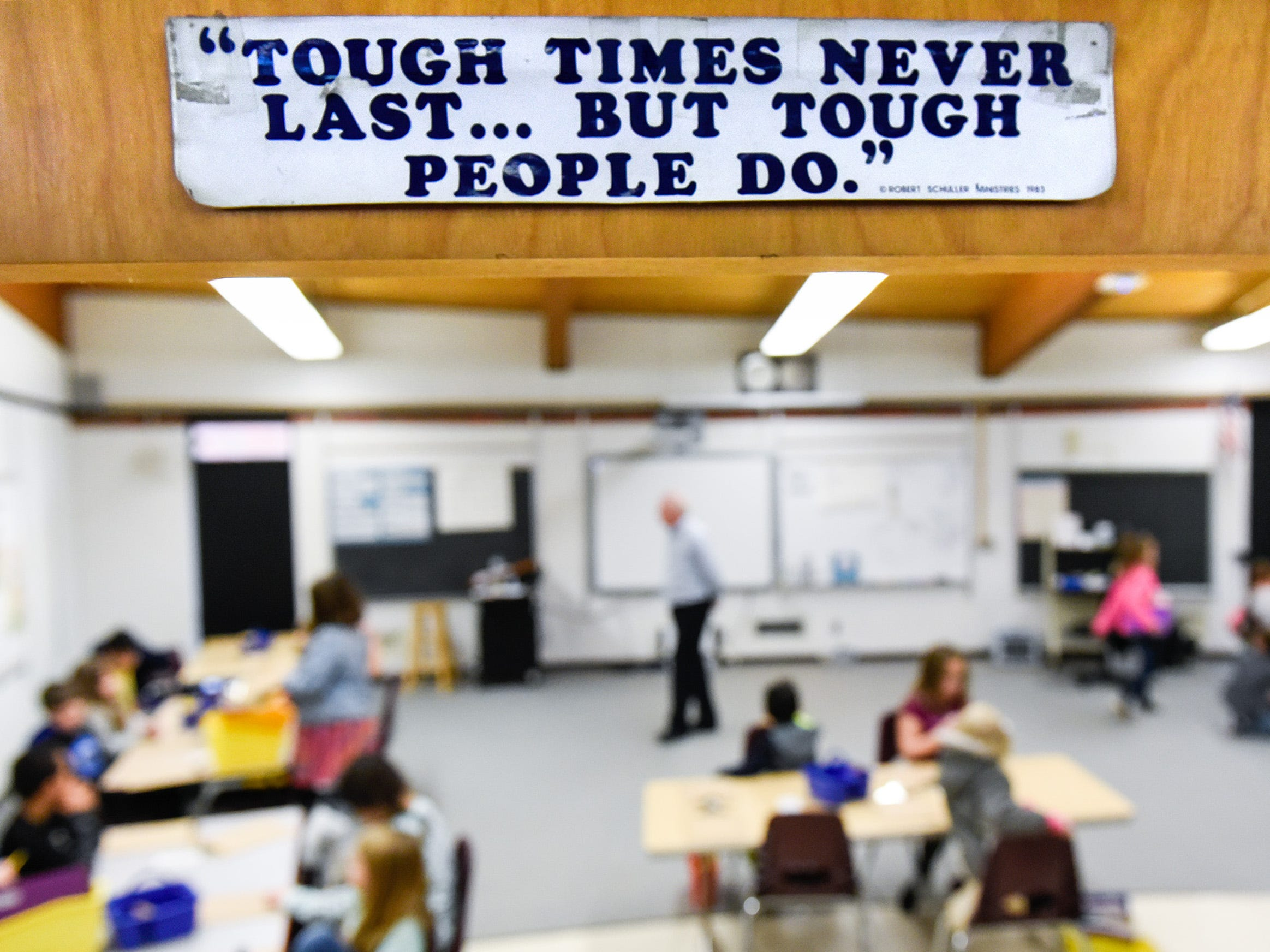 Teacher Brad Olson placed a sign over the door of his new classroom area Tuesday, Jan. 15, after a fire damaged classrooms at Pleasantview Elementary School in Sauk Rapids.