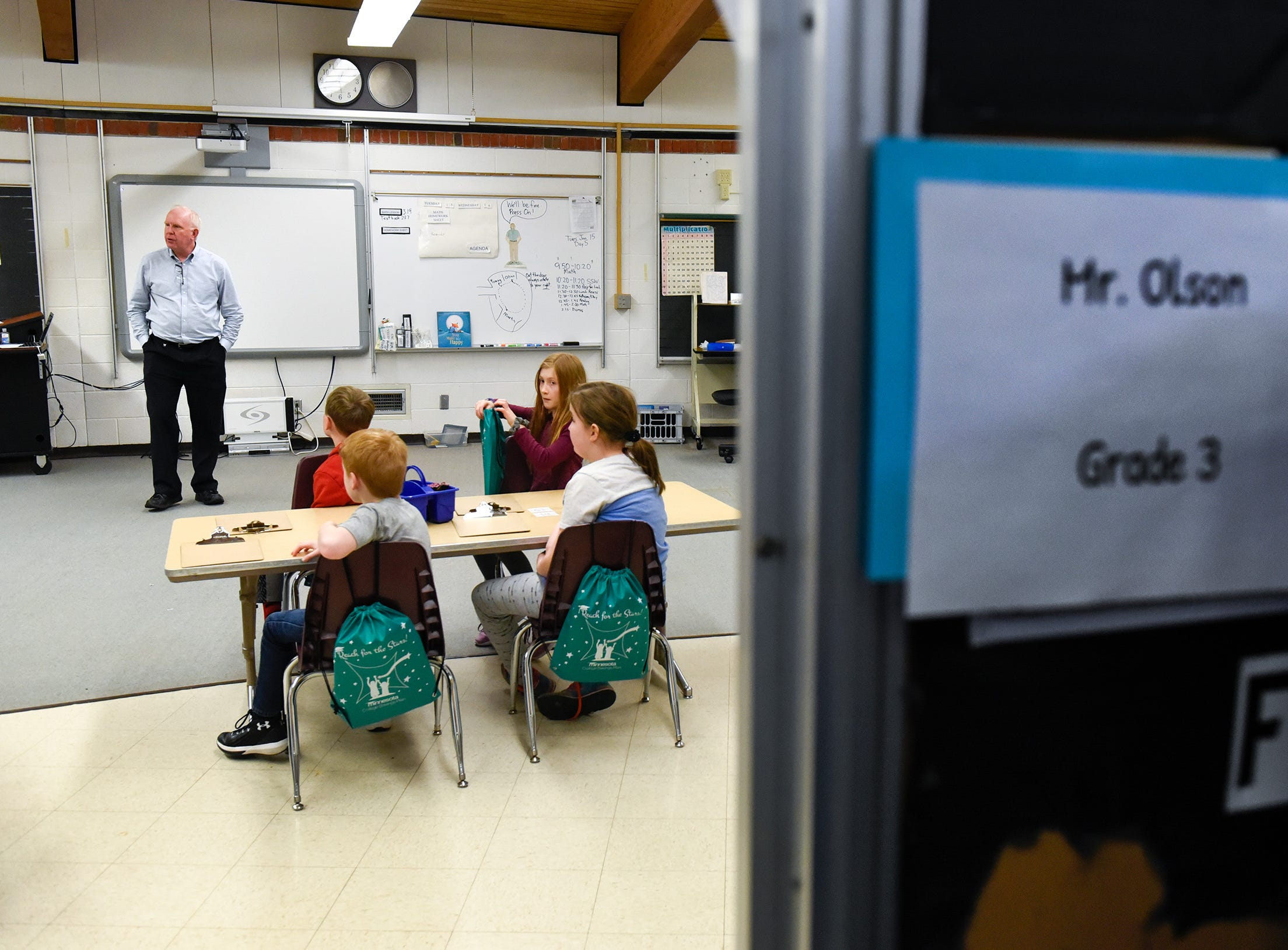 Teacher Brad Olson gets his students settled into their new classroom area Tuesday, Jan. 15, after a fire damaged classrooms at Pleasantview Elementary School in Sauk Rapids.