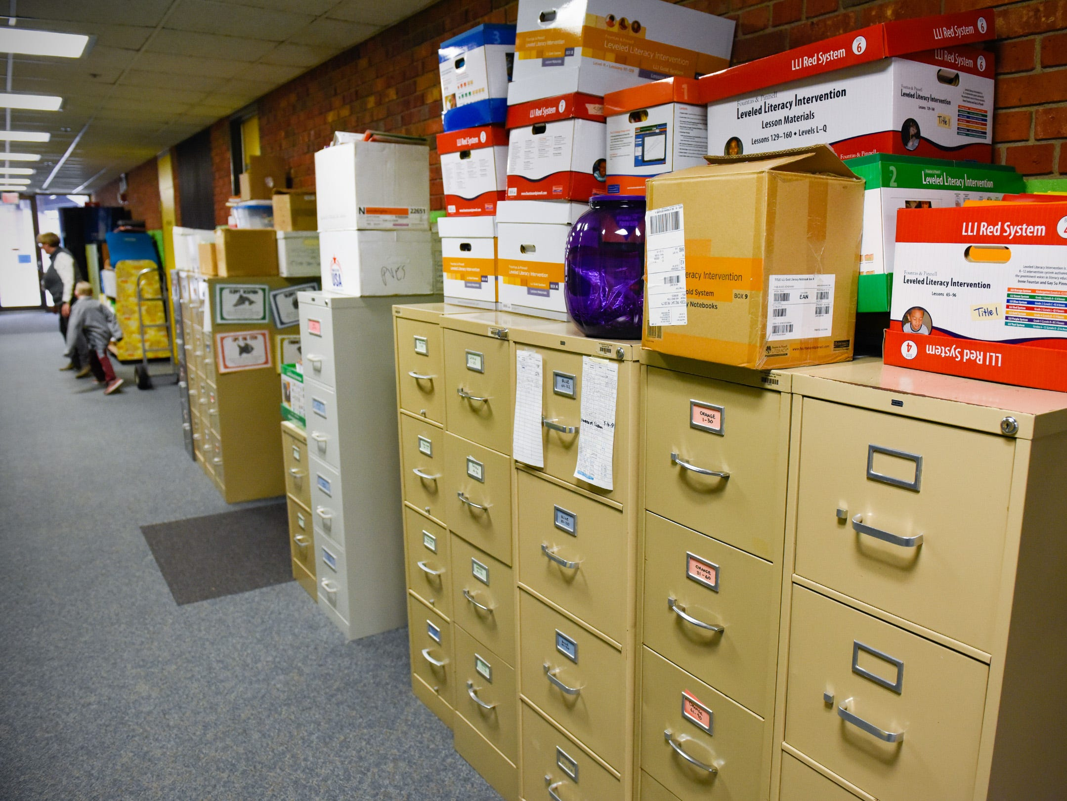 File cabinets and boxes are moved from a storage area to the hallway to create a classroom Tuesday, Jan. 15, after a fire displaced four classrooms at Pleasantview Elementary School in Sauk Rapids.