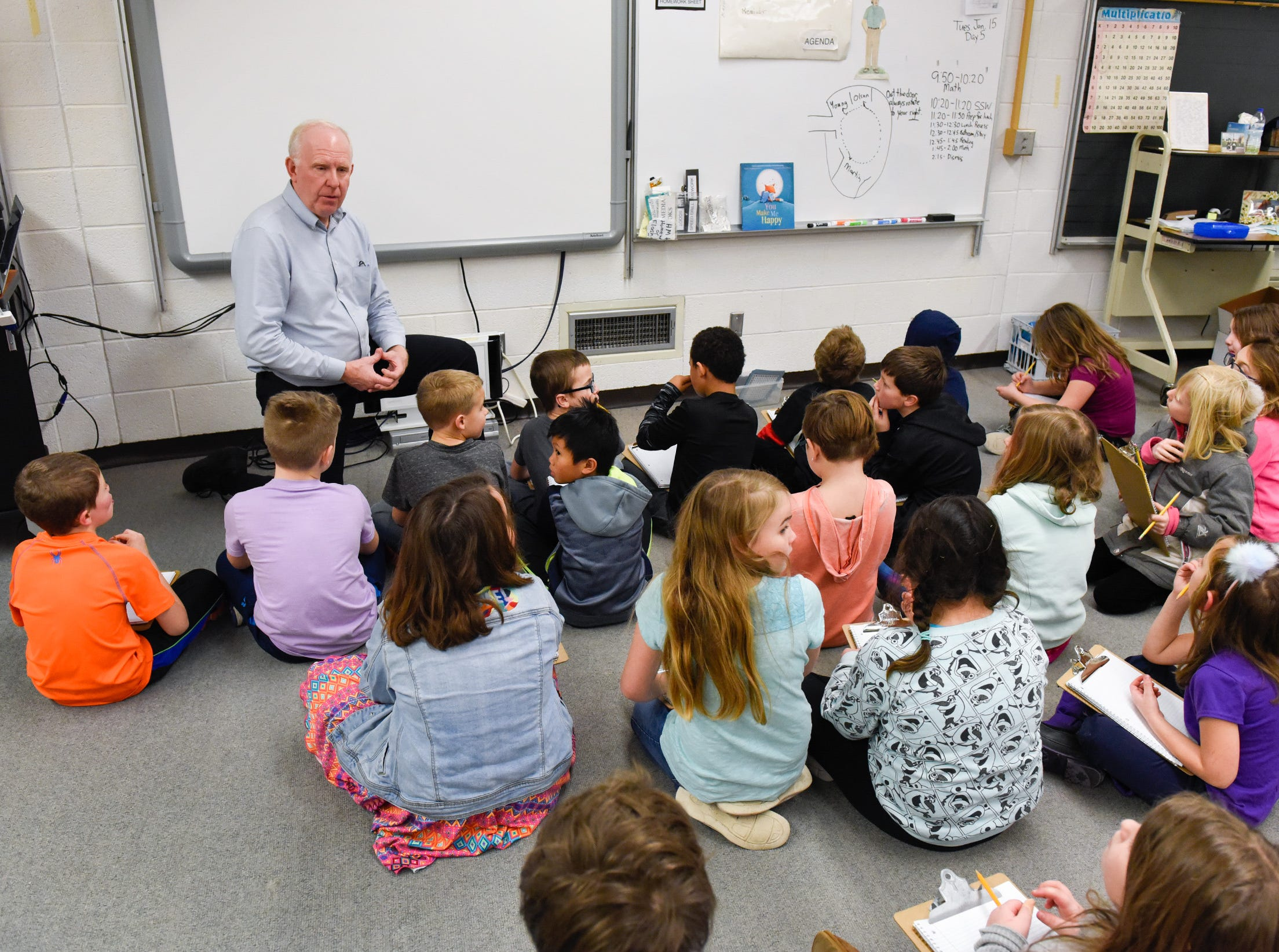 Teacher Brad Olson talks with students as they settle into their new classroom area Tuesday, Jan. 15, after a fire damaged classrooms at Pleasantview Elementary School in Sauk Rapids.