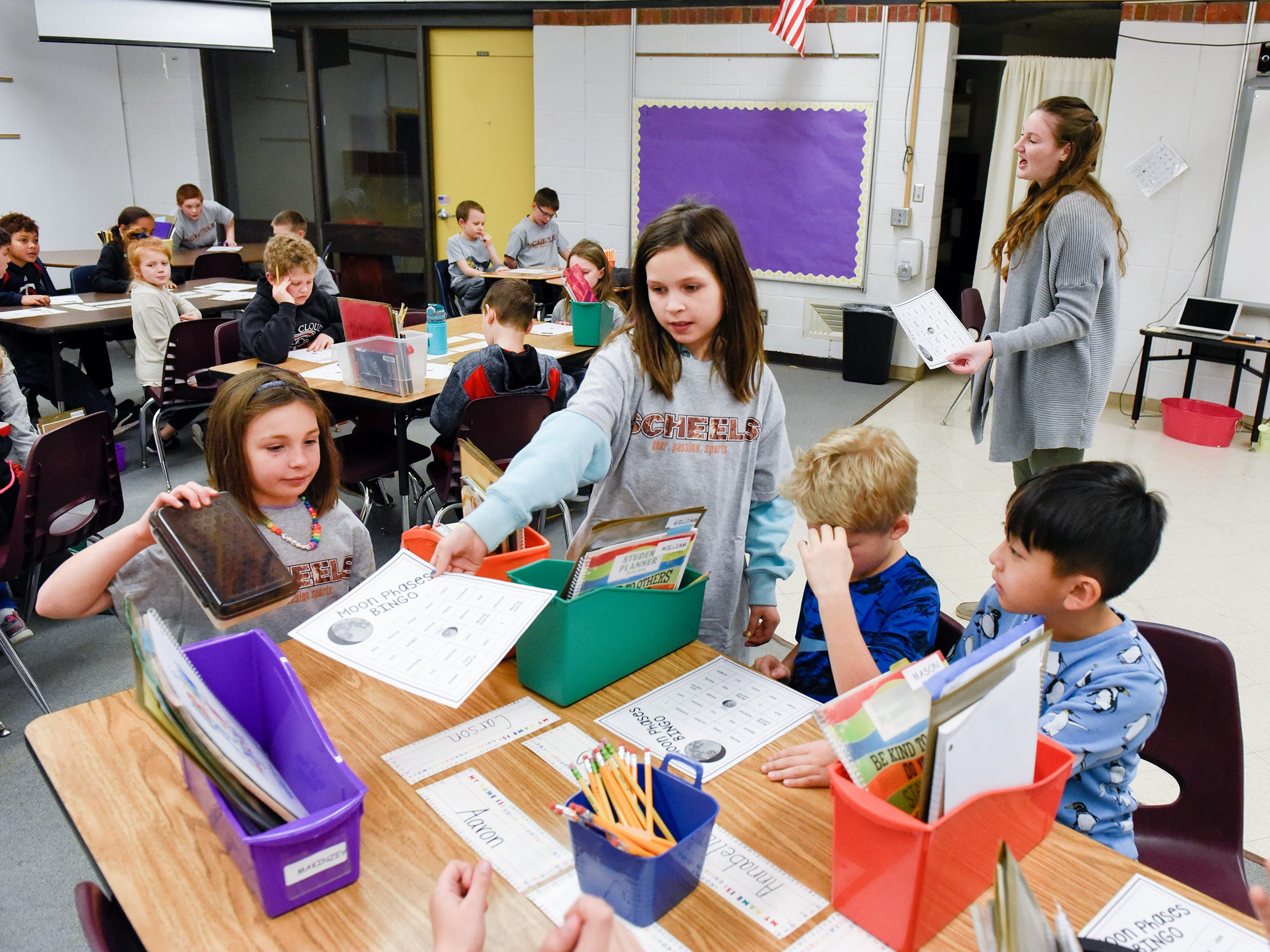 Teacher Emily Young gets her students started on a science game in their new classroom Tuesday, Jan. 15, after a fire damaged classrooms at Pleasantview Elementary School in Sauk Rapids.