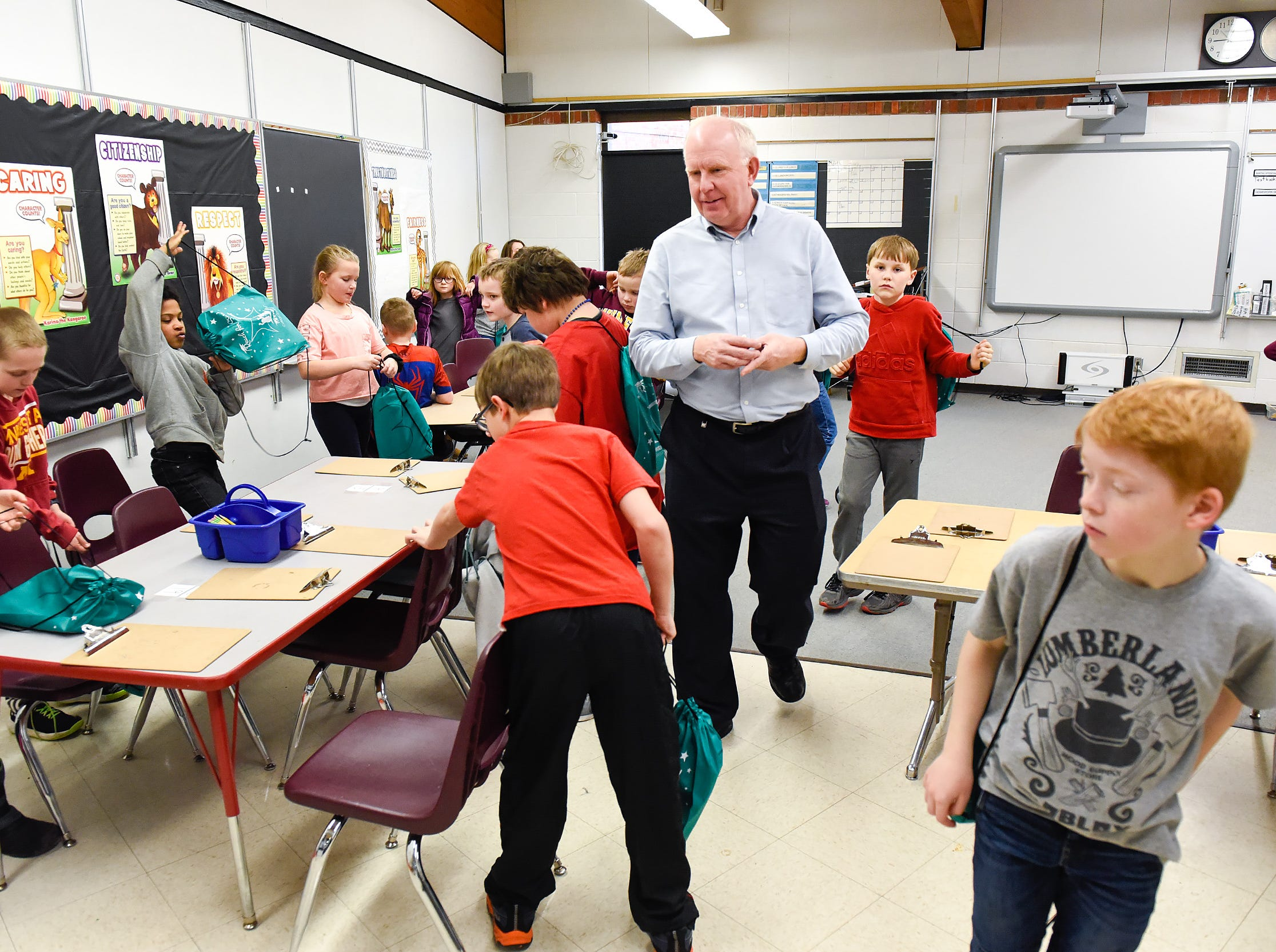 Teacher Brad Olson gets his class settled into their new classroom area Tuesday, Jan. 15, after a fire damaged classrooms at Pleasantview Elementary School in Sauk Rapids.