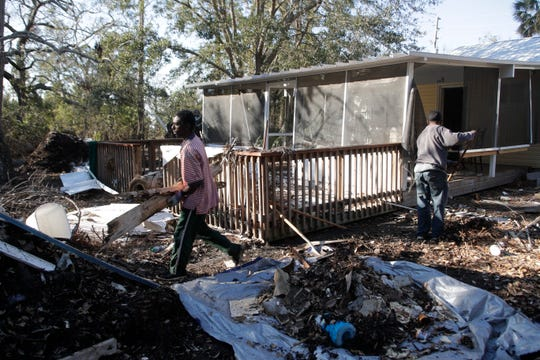 Brothers Bradley and Gary Owens work for Gulf Building Company to clear debris from the yard of a home in Port St. Joe Tuesday, Jan. 15, 2019, three months after Hurricane Michael destroyed it in October.