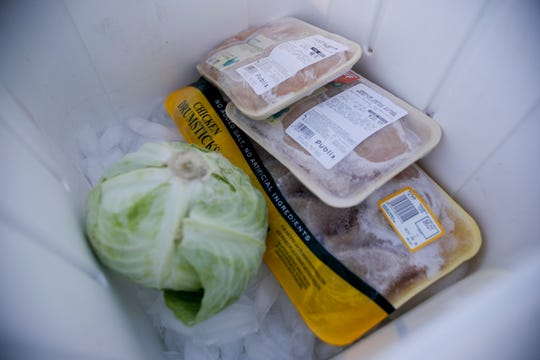 Transportation Security Administration employee Brian Burke fills a cooler in the back of his truck with poultry and cabbage provided to him by Second Harvest of the Big Bend before he goes into work for his shift at Tallahassee International Airport where he is working without pay during the government shutdown Thursday, Jan. 17, 2019.
