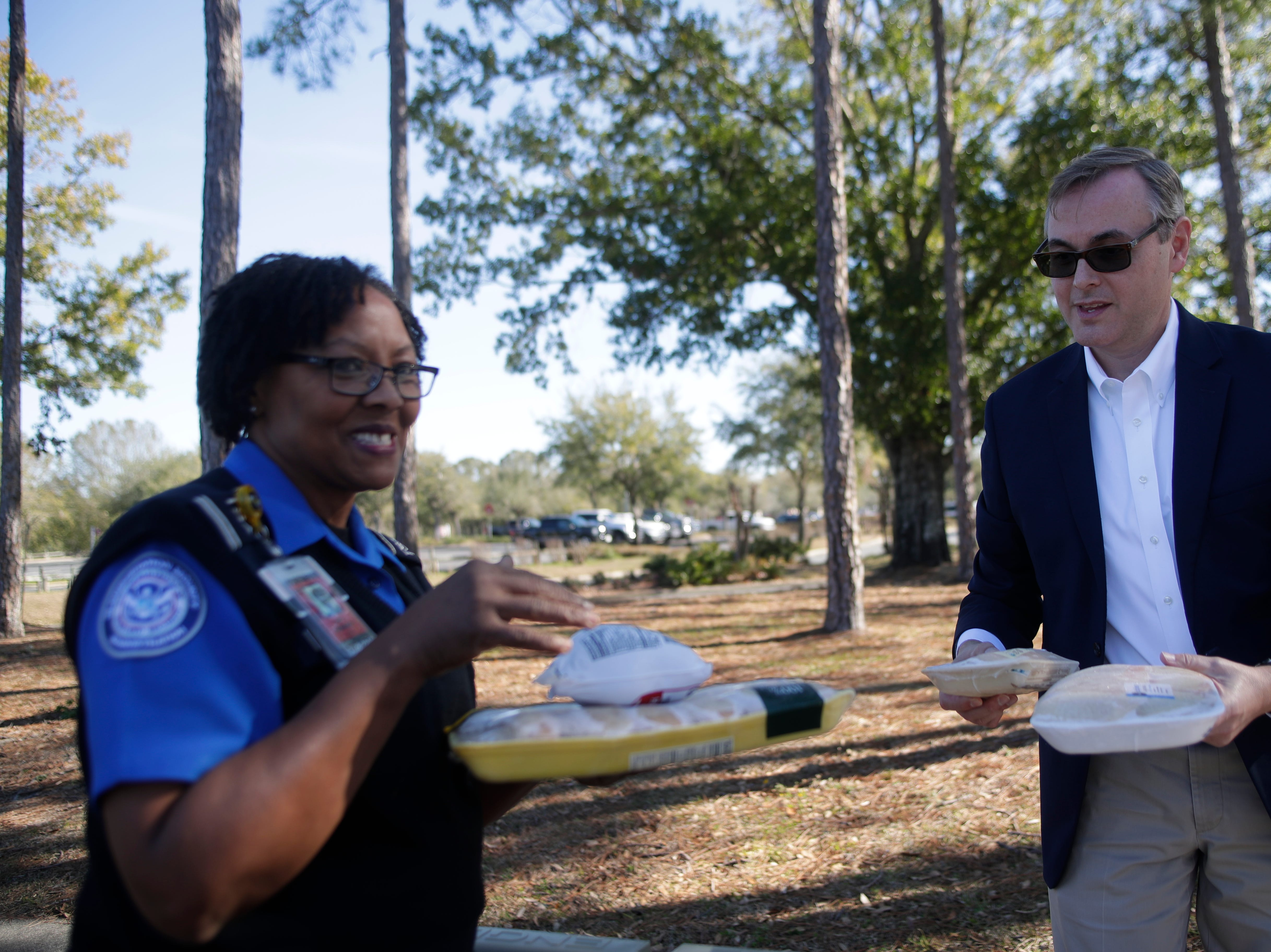 Second Harvest of the Big Bend CEO Rick Minor hands out poultry and other food to Transportation Security Administration employee Mae Speights at the Tallahassee International Airport Thursday, Jan. 17, 2019.