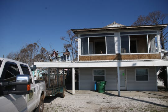 Albert Milton and his second cousin Shag Willis eat their lunch of Subway sandwiches on what once was a wrap around deck on the second story of Milton's vacation home along U.S. Highway 98 in St. Joe Beach as they continue to work to get belongings out of the home three months after Hurricane Michael destroyed it.