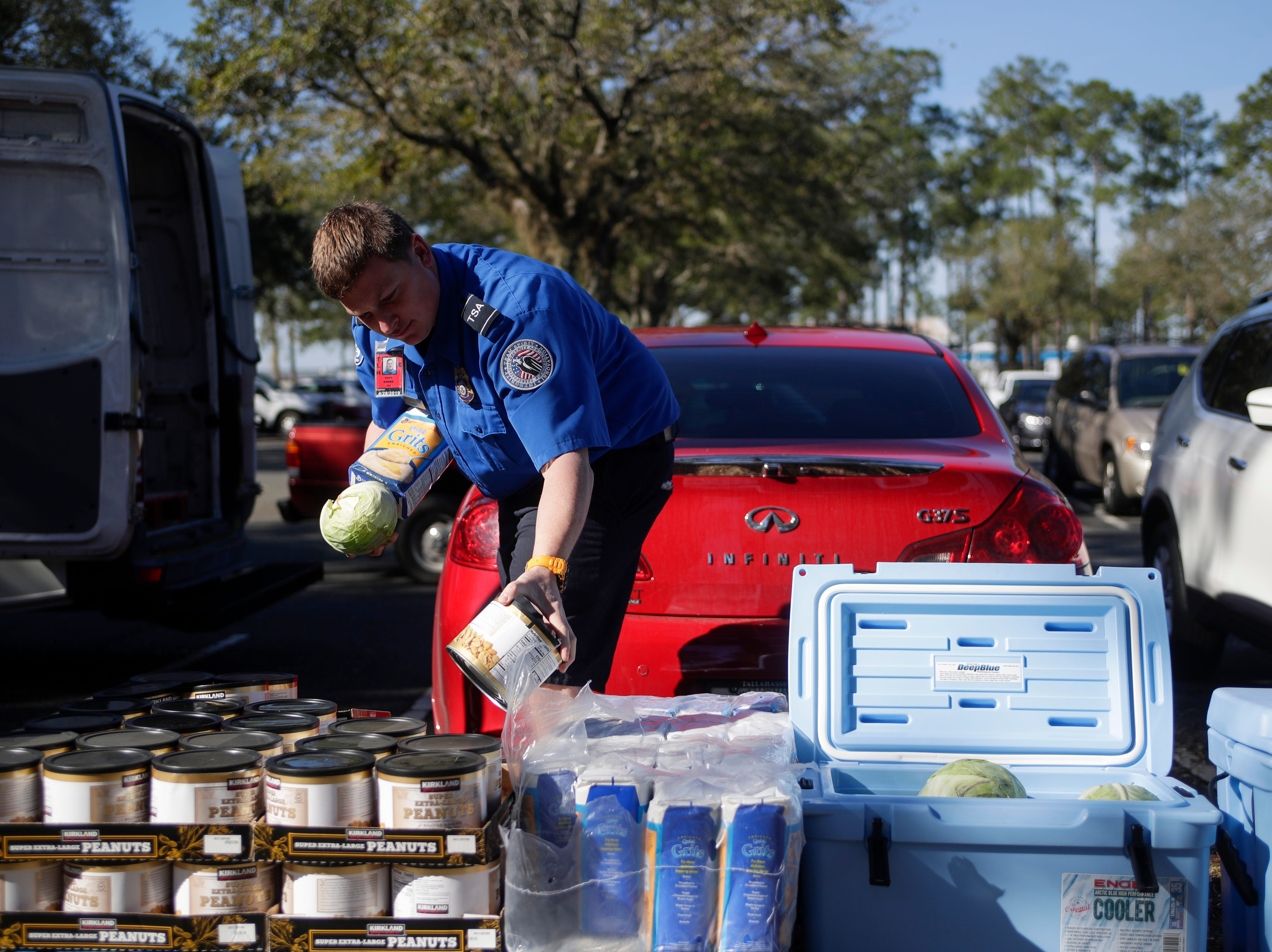 Transportation Security Administration employee Brian Burke chooses a can of peanuts provided by Big Bend Second Harvest to help feed his family of four children as he works without pay at the Tallahassee International Airport Thursday, Jan. 17, 2019.