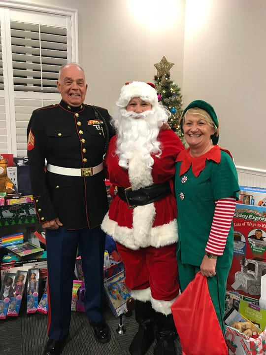 Sgt. Peter Sayles, left, of the Marine Corps League, Vietnam Veterans of America and representative for Toys for Tots Indian River County shares a moment with Santa and Elf Carol Hawk as Sayles picks up Christmas gifts from the Realtors Association of Indian River County. Santa was played by  Ashley Osteen, association education and communications coordinator. Hawk is CEO of the association.