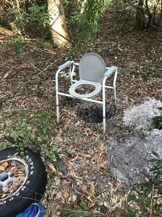 A commode chair is perched over a hole in the ground on Harper's property.
