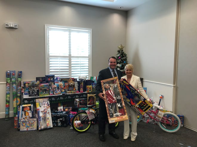 RealtorsAssociation of Indian River County 2019 President Andrew Harper and Executive Officer Carol Hawk with the toys collected at the association's annual holiday part for the Indian River County Toys for Tots.