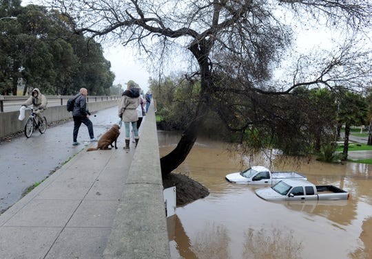 A couple of cars sit nearly submerged near the Main Street Bridge in Ventura after the latest storm caused flooding in the area Thursday.