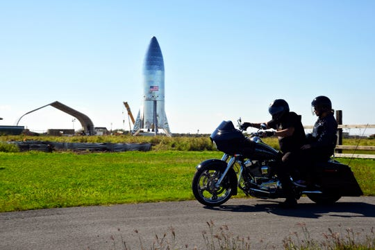 In this Jan. 12, 2019 file photo, a motorcyclist rides near the SpaceX prototype Starship hopper at the Boca Chica Beach site in Texas. SpaceX says it will build its Mars spaceship in Texas instead of at the Port of Los Angeles.